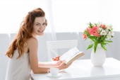 Fotografie happy young woman reading book while sitting at table with coffee cup and flowers in vase
