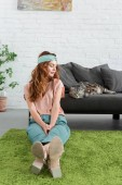 Photo beautiful young woman sitting on floor near her tabby cat at home