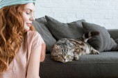 attractive young woman smiling at adorable tabby cat at home