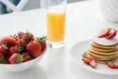Fotografie zblízka střílel z chutné palačinky s jahodami a pomerančovým džusem