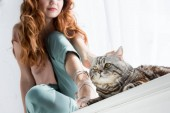 cropped shot of young woman petting tabby cat while sitting on windowsill at home