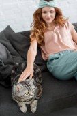 beautiful young woman petting tabby cat while sitting on couch at home