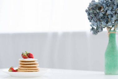 tasty pancakes with strawberries and flowers in vase on table
