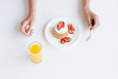 cropped shot of woman having orange juice and pancakes with strawberry for breakfast