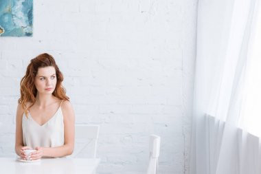 thoughtful young woman with cup of coffee in front of white brick wall looking at window