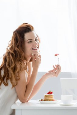 beautiful young woman eating pancakes with strawberry at home