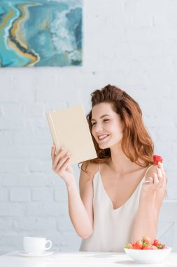 happy young woman with coffee and strawberry reading book at home