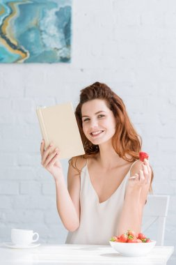 happy young woman with book and strawberry sitting at table