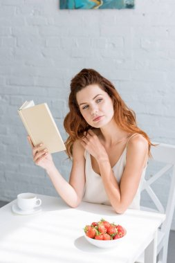 thoughtful young woman with book and cup of coffee sitting at table