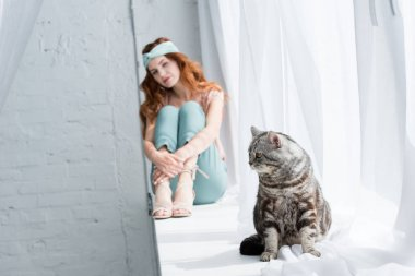 beautiful young woman sitting on windowsill with tabby cat on foreground
