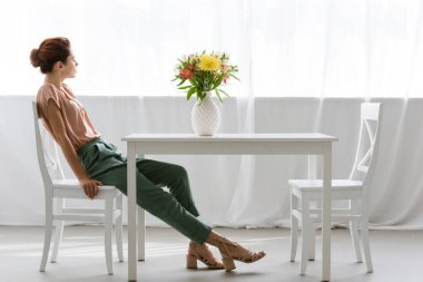 side view of attractive young woman sitting at table with beautiful flowers in vase alone at home
