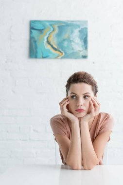 thoughtful young woman sitting at table in front of white brick wall with picture