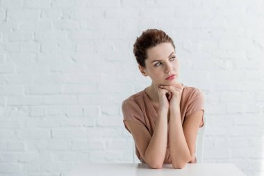 thoughtful young woman sitting at table in front of white brick wall