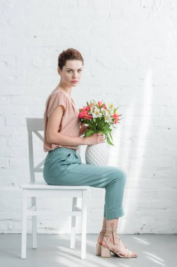attractive young woman holding vase with flowers while sitting on chair in front of white brick wall and looking at camera