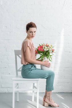 side view of beautiful young woman holding vase with flowers while sitting on chair in front of white brick wall