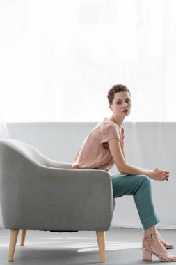 side view of attractive young woman sitting on armchair at home