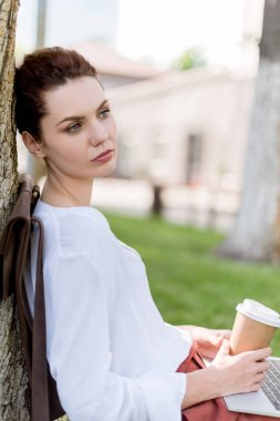 thoughtful young woman with laptop and paper cup of coffee leaning back on tree trunk in park and looking away