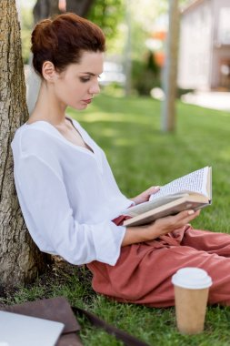 side view of young woman leaning back on tree trunk in park and reading book