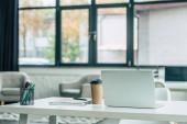 laptop, jednorázový kelímek, držák na notebook a pero na bílém stole v moderní kanceláři