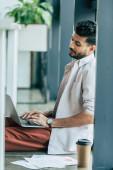 přemýšlivý podnikatel v ležérní oblečení pomocí notebooku, zatímco sedí na podlaze v kanceláři