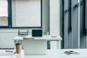 kancelářské stoly s notebooky, káva na cestu a sklenice vody, notebooky a podnosy s dokumenty