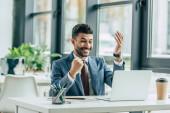 vzrušený podnikatel ukazuje vítězný gesto, zatímco sedí na pracovišti v blízkosti notebooku