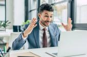 překvapený podnikatel ukazující wow gesto při pohledu na notebook