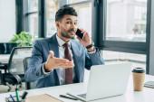 pozitivní podnikatel ukazuje rukou na notebook, zatímco mluví na smartphone