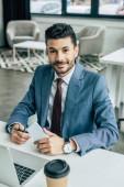 mosolygós üzletember néz kamera, miközben ül a munkahelyen közelében laptop és gazdaság okostelefon