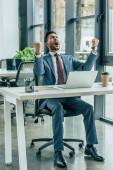 šťastný podnikatel křičí a ukazuje vítězný gesto při sezení na pracovišti