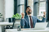 happy businessman looking up and showing winner gesture while sitting at workplace