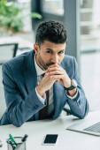přemýšlivý podnikatel dívá do kamery, zatímco sedí na pracovišti