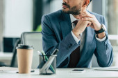 oříznutý pohled na podnikatele sedícího na pracovišti se složenýma rukama