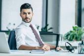 Fotografie Selbstbewusster Geschäftsmann blickt am Arbeitsplatz in die Kamera