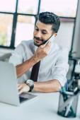 selektivní zaměření usměvavý podnikatel pomocí notebooku při mluvení na smartphone