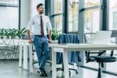 mladý sebevědomý podnikatel stojí u stolu a dívá se jinam