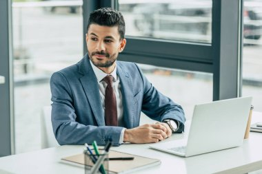 Smiling businessman looking away while sitting at workplace near laptop stock vector