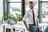 fiatal üzletember mosolyog és félrenéz, miközben a munkahelyén áll