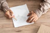 oříznutý pohled na důchodce s Alzheimerovou chorobou kreslící lidskou hlavu a mozek