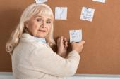 Selektiver Fokus einer Seniorin mit Alzheimer-Krankheit, berührendes Papier mit Wer bin ich-Briefen