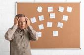 nyugalmazott férfi Alzheimer-kór érintő fej és áll a fedélzeten papírok és levelek