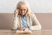 senior woman with alzheimer disease reading book and touching glasses