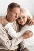 frustrata pensionato donna abbracciando marito anziano con malattia mentale