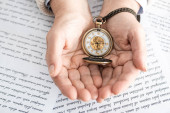 Fotografie top view of senior woman holding compass near papers with letters