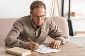 idős férfi mentális betegség rajz papíron közel könyv otthon