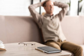 selective focus of table with glasses and notebook near senior man