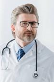 pohledný lékař v bílém plášti při pohledu na kameru v nemocnici