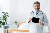 usmívající se lékař v bílém plášti drží digitální tablet s kopírovacím prostorem v nemocnici