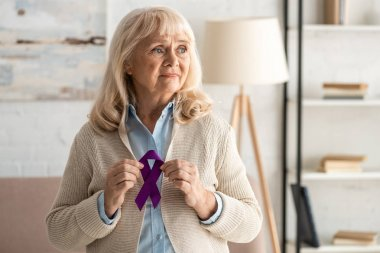 Sad retired woman holding purple ribbon at home stock vector