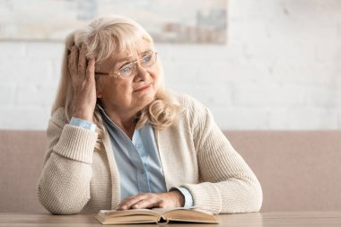 Upset senior woman in glasses sitting near book stock vector